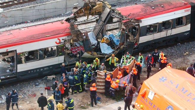 Rescue workers cover up bodies March 11, 2004, alongside a bomb-damaged passenger train, following a number of explosions in Madrid, Spain.
