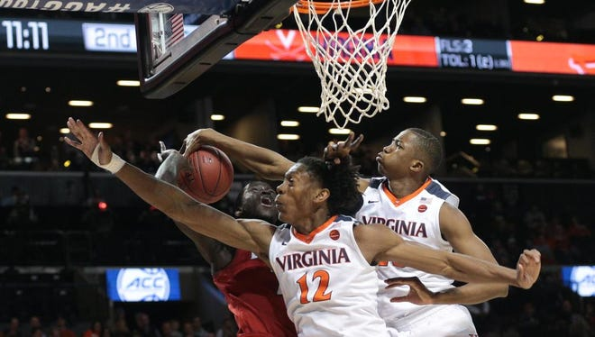 Mar 8, 2018; New York, NY, USA; Virginia Cavaliers guard De'Andre Hunter (12) and forward Mamadi Diakite (25) defend against Louisville Cardinals forward Deng Adel (22) during the second half of a quarterfinals game of the 2018 ACC tournament at Barclays Center at Barclays Center. Mandatory Credit: Nicole Sweet-USA TODAY Sports
