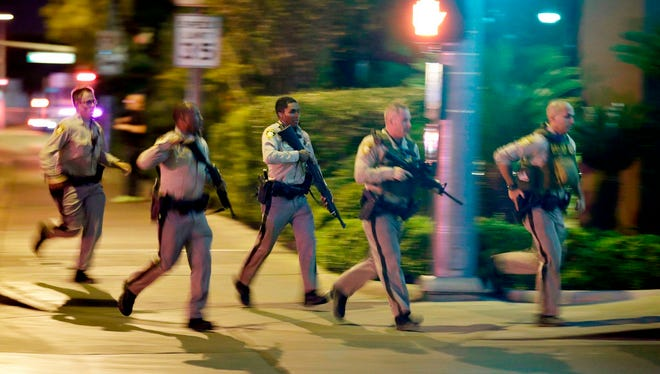 In this Oct. 1, 2017, file photo, police run toward the scene of a shooting near the Mandalay Bay resort and casino on the Las Vegas Strip in Las Vegas. Police in Las Vegas plan to release witness statements and officer reports of the Oct. 1 gunfire that killed 58 people and injured hundreds in the deadliest mass shooting in modern U.S. history.