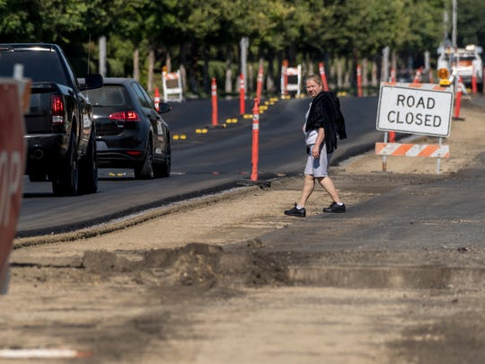 A pedestrian crosses traffic on Houston Avenue between Mooney and Demaree while construction continues on Monday, June 25, 2018. Traffic has been moved to the north side while the south side is repaved.