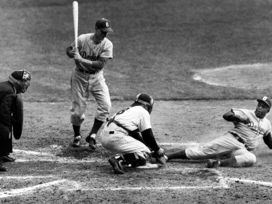 Jackie Robinson safely steals home plate under the tag Yankees catcher Yogi Berra in the 1955 World Series (AP).