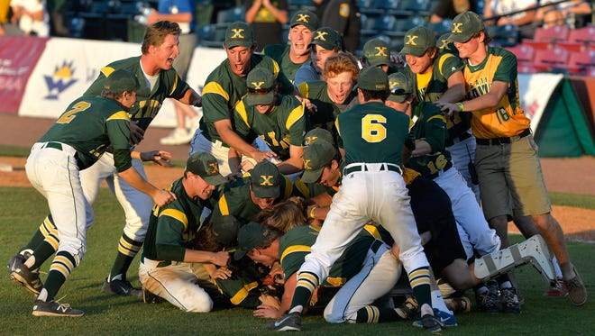 Members of the St. Xavier baseball team celebrate following their 1-0 victory in their Kentucky State baseball championship game Against Campbell County, Saturday, June 18, 2016 in Lexington Ky. (Timothy D. Easley/Special to the C-J)