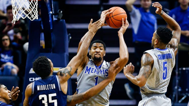 University of Memphis forward Dedric Lawson (middle) grabs rebound in front of Jackson State University defender Janarius Middleton (left) and teammate Markel Crawford (right) during first half action at the FedExForum.