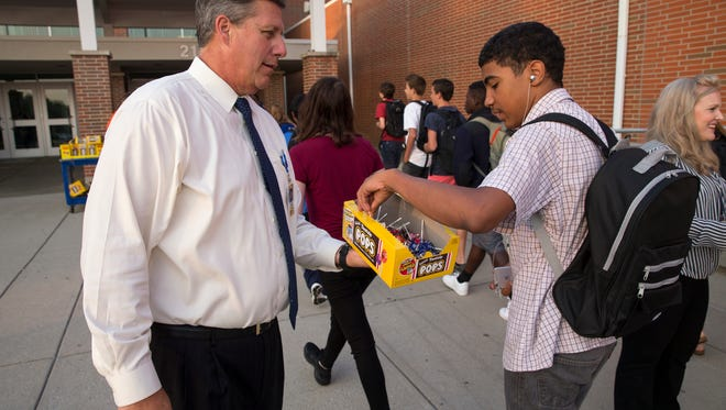 Thomas Harmas, the new Carmel High School principal, hands out candy to arriving students on the first day of classes, Carmel, Tuesday, August 15, 2017.