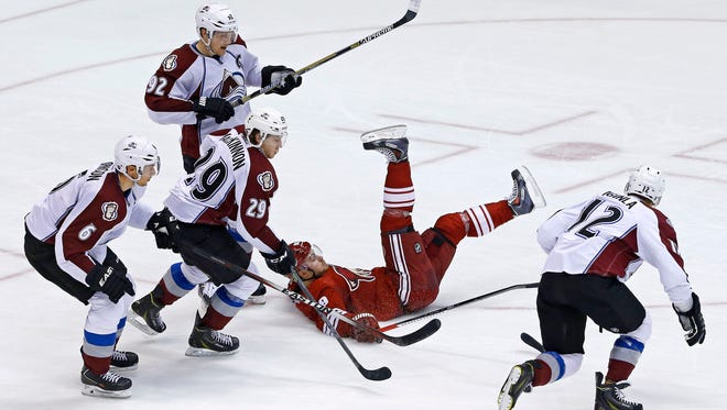 Arizona Coyotes left wing Mikkel Boedker (89) falls to the ice after a hooking penalty by Colorado Avalanche Nathan MacKinnon during the second  period of their NHL game Tuesday, Nov. 25, 2014 in Glendale, Ariz.