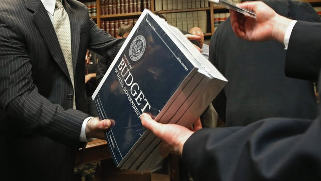 Senate Budget Committee staff members hand out copies of the Obama administration's proposed budget in April.