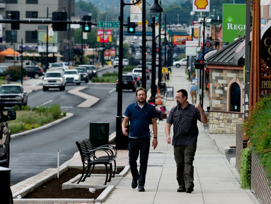 Pedestrians walk along Cumberland Avenue in Knoxville,