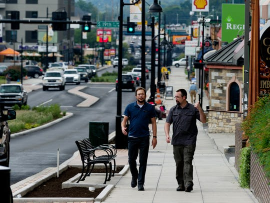 Pedestrians walk along Cumberland Avenue in Knoxville, Tennessee on Wednesday, August 16, 2017.