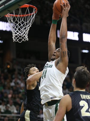 Michigan State's Nick Ward scores against Purdue guard Carsen Edwards, Feb.10, 2018 in East Lansing.