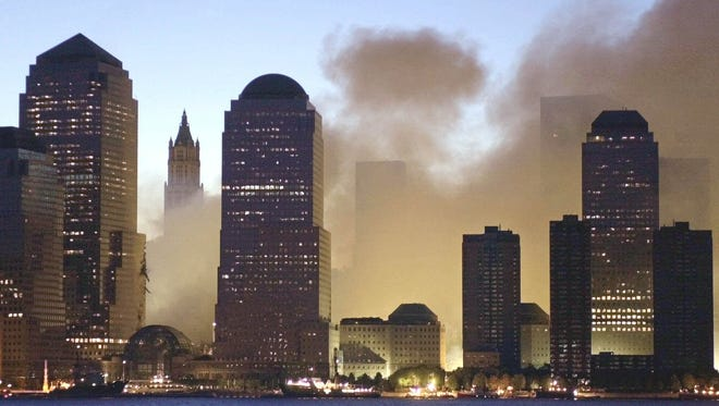 As dawn breaks over New York, smoke rises from lower Manhattan following the destruction of buildings at the World Trade Center in New York, Wednesday, Sept. 12, 2001.  Two hijacked commercial aircraft crashed into the center's towers, which were previously visible looming over the buildings at left. (AP Photo/Charles Krupa)