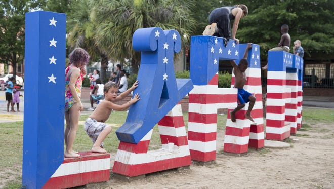 Children play on the red, white and blue painted Lafayette sign at Parc Sans Souci, part of the city's Independence Day celebration in downtown Lafayette.