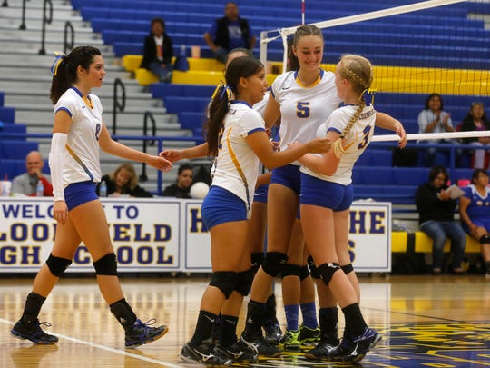 Bloomfield players celebrate after defeating Zuni in three sets on Tuesday at Bobcat Gym in Bloomfield.