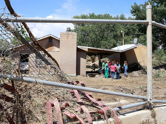 Family members and friends gather at the site of one of the damaged homes on Saturday in the Salt Wash area of north Shiprock.
