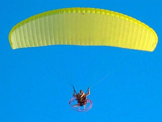 A powered parachuter flies over the beaches of Pass-A-Grille, Fla.