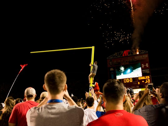 Students help tear down a goal post as fireworks go