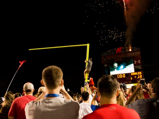 Students help tear down a goal post as fireworks go off in the distance after Austin Peay wins its first game since 2014, beating Morehead State 69-13 on Sept. 16, 2017.