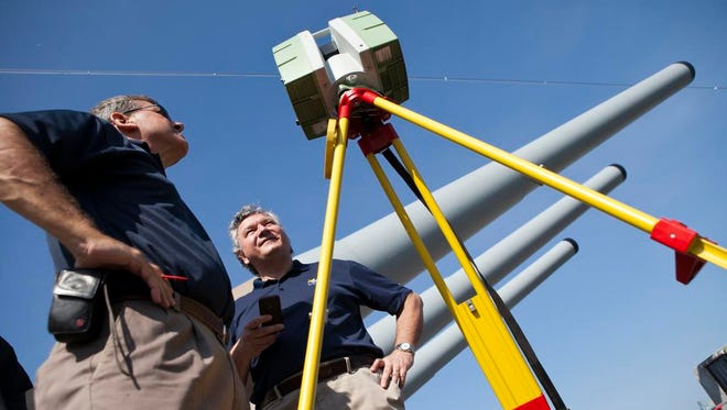 Frank Lenik of Leica Geosystems, left, and Chris Zmijewski, Vice President of HAAG Global 3D Solutions, check on a camera that creates 3D scans while working on the Battleship New Jersey, Tuesday, August 19, 2014 in Camden.