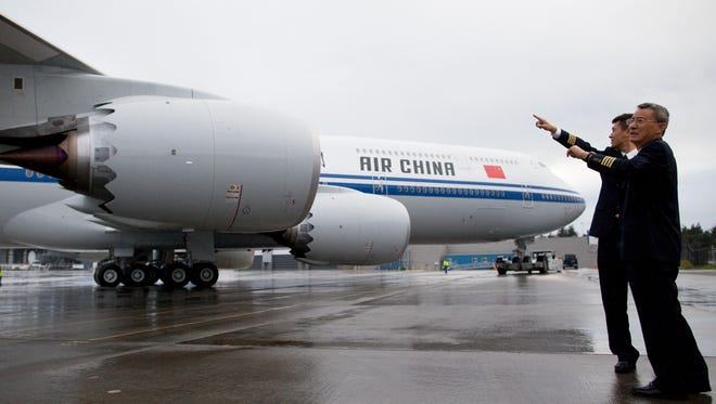 Captain Zhou Daning (left), 39, speaks with his father, Capt. Zhou Dianzhuo, 66. The elder Zhou piloted Air China's 747-400 fleet, while his son Daning will fly the newest -8i model.