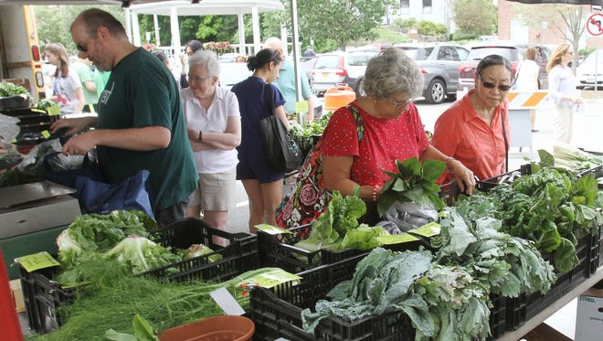 People look over some of the fresh produce from one of the many vendors at the Pleasantville Farmers Market in Pleasantville July 2, 2016.