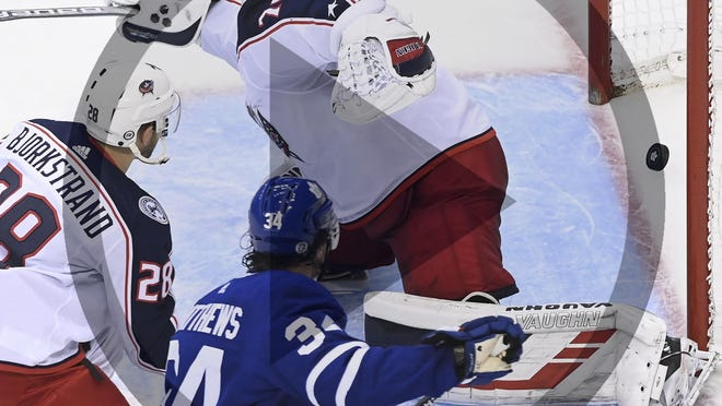Toronto Maple Leafs center Auston Matthews (34) scores past Columbus Blue Jackets goaltender Joonas Korpisalo (70) as Blue Jackets right wing Oliver Bjorkstrand (28) looks on during second period NHL Eastern Conference Stanley Cup playoff action in Toronto on Tuesday, Aug. 4, 2020.