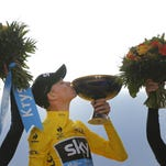 Chris Froome, center, kisses the trophy as he stands on the podium with second-place finisher Nairo Quintana, left, and third-place finisher Alejandro Valverde at the end of the Tour de France on Sunday in Paris.