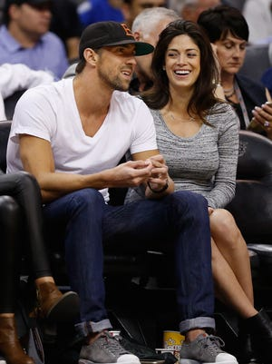 Olympic swimmer Michael Phelps and fiancee Nicole Johnson attend an NBA game between the Phoenix Suns and the Golden State Warriors at Talking Stick Resort Arena on Feb. 10, 2016 in Phoenix.