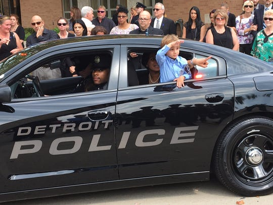 Alexander Steil, 3, salutes out the window of a police car in the funeral procession Sept. 23, 2016, for his father, Detroit Police Sgt. Kenneth Steil. Police Chief James Craig promoted Steil to captain at the funeral at St. Joan of Arc Catholic Church.Ê