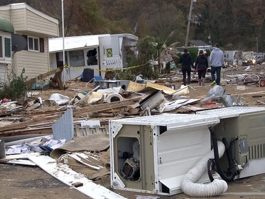 People walk through debris at the Paradise Park mobile home community in Highlands after superstorm Sandy.