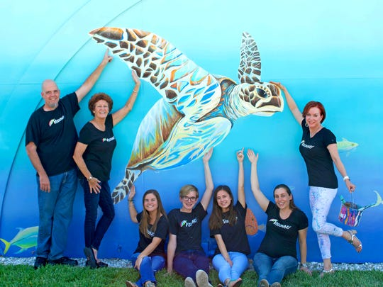 Visionary School of Arts staff, from left, Mike Nolan, Andi Harness, Madisyn Derita, Christopher Carnes, Abigail Afong, Alicia Jones and Lynne Barletta, school founder, were among the artists who painted the Catch the Wave of Hope mural.