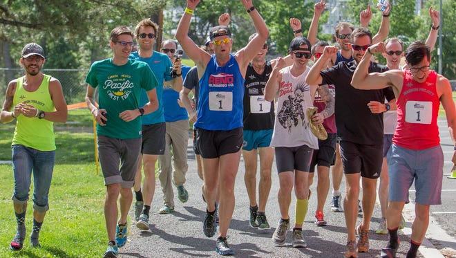 Dave Zaski, center in blue, leads his team the Runny Bums across the finish line during the 12th Annual Reno-Tahoe Odyssey Relay Run on Saturday, June 4, 2016.  The Runny Bums won the event for a second year in a row with a time of 17 hours, 30 minutes and 44 seconds.