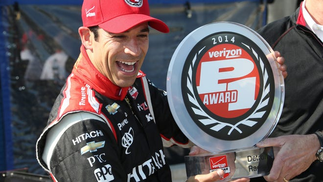 Driver Helio Castroneves reacts as he poses with the pole position trophy for the first IndyCar Detroit Grand Prix in Detroit, Saturday.
