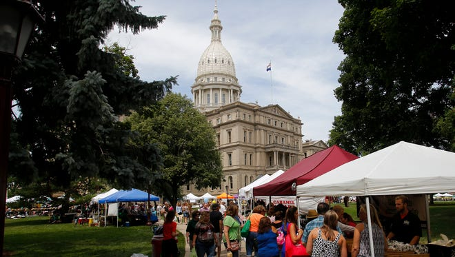 People peruse booths Thursday, July 28, 2016, at the Capitol Farmers Market on the Capitol lawn.  It is the first of three slated for this summer.  About 70 vendors from throughout the state are selling Michigan-produced products.