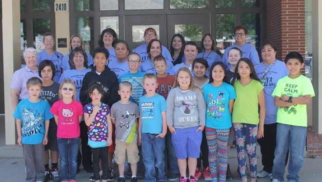 """Staff of Heights Elementary School showed their support for their students in military families by wearing purple during Purple Up Day last April. This year, APS is hosting """"A Walk in Their Shoes,"""" which is a parade and celebration on April 20."""
