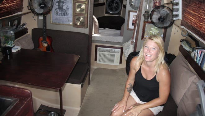 Justine Slocum, better known as Skipper.  shows her proudly inside the cabin of her sailboat, Spray