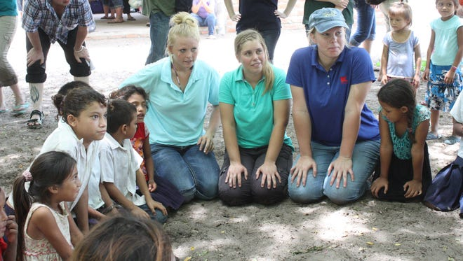 "Audrey Hoey plays ""Pato, Pato, Gonoz"" (Duck, Duck, Goose) with children in Honduras."