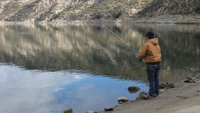 Jed Wilson, of Bloomfield, reels in a line from Navajo Lake in a futile salmon snagging attempt on Saturday.