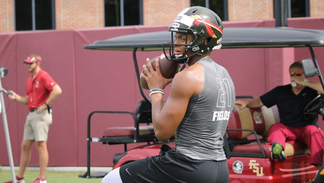 FSU coach Jimbo Fisher watches five-star quarterback prospect Justin Fields throw during the Jimbo Fisher camp  this past weekend.