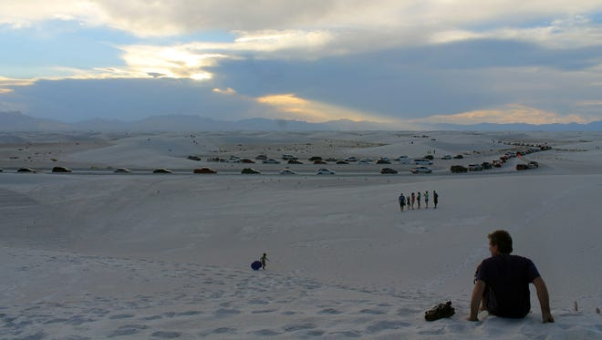 In this file photo, hundreds of cars make their way into White Sands National Monument for a Full Moon Night event in 2016.