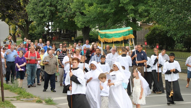 St. Peter Catholic Church conducted their annual Eucharistic processions through theneighborhood on the Feast of Corpus Christi, June 18, 2017. The Rev.William Hahn led the procession. The parishioners processed through the neighborhood singing hymns of praise.