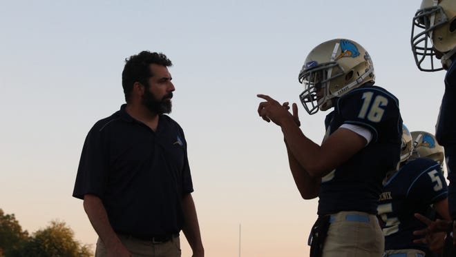 Phoenix Day School for the Deaf quarterback Cesar Aranda (16) talks to head coach Dave Huber (left) on the sidelines against Williams junior varsity on Thursday, Oct. 5, 2017 in Phoenix, Ariz.