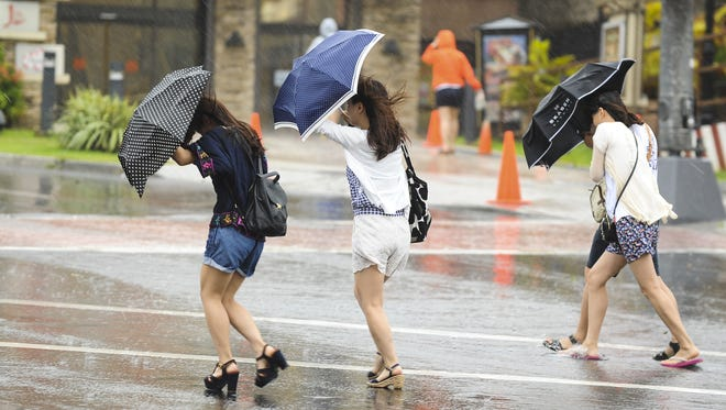 Women push forward with their umbrellas in a rainshower as they cross the street near the T Gallery Guam in Tumon in October 2015.