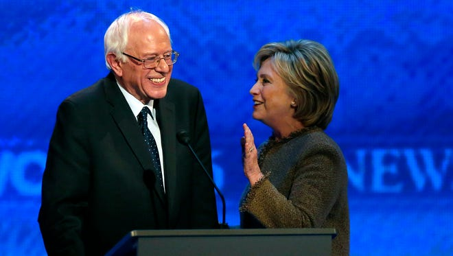 Hillary Clinton, right, speaks to Bernie Sanders during a break at the Democratic presidential primary debate Saturday, Dec. 19, 2015, at Saint Anselm College in Manchester, N.H. (AP Photo/Jim Cole)