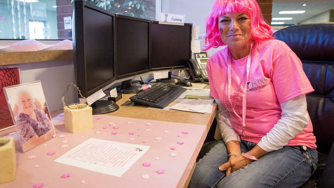 Tammy Hyre, an ASONS employee, works the front desk at the company with a memorial to her aunt Friday afternoon during Pink Day at the office.