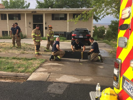 St. George Fire Department firefighters roll up their hoses after extinguishing a fire on the back deck of the home in the background Tuesday, Aug. 25, 2015.