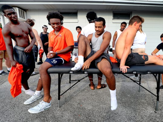 Blackman football players wait to get taped by trainer Kelly Stephens.