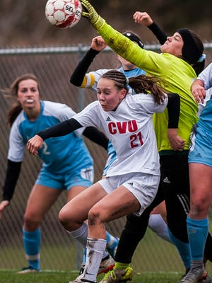 South Burlington keeper Bailey Burt punches the ball away, over CVU #21 Josie Pecor during their girl's soccer semifinal in Hinesburg on Wednesday, Nov. 1, 2017. CVU pulled off the win in sudden-death overtime, 1-0.