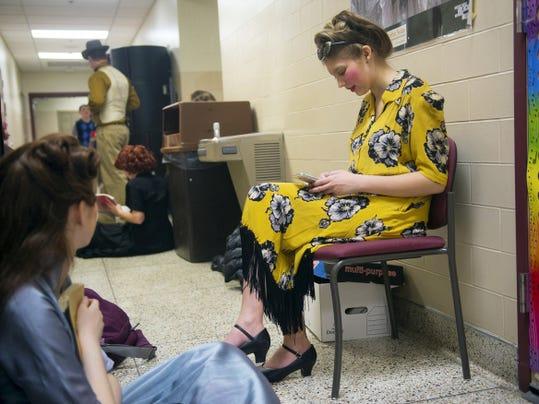 Ensemble cast member Tori Light checks her phone before a rehearsal run-through at Hanover High School on April 7.
