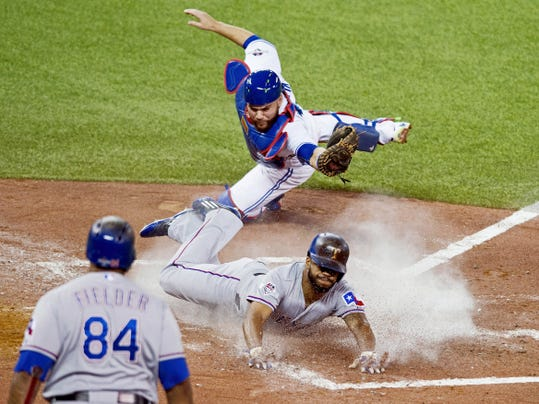 The Texas Rangers' Delino DeShields, center, scores past Toronto Blue Jays catcher Russell Martin during the third inning of Game 1 of the American League Division Series in Toronto.