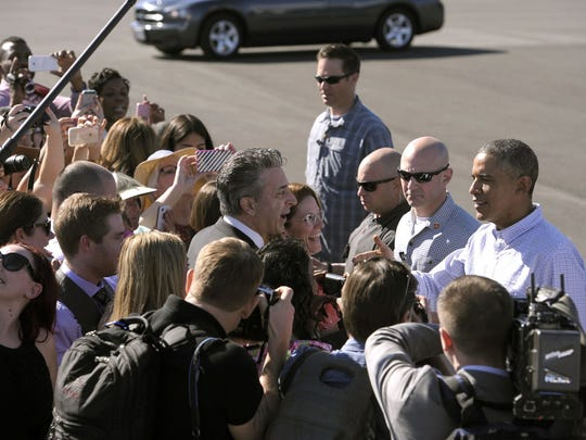 President Barack Obama shakes hands with greeters.