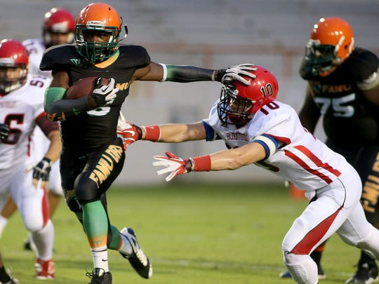 FAMU DRS running back Sam Thomas stiff arms a Blountstown defender during a 2014 game. Thomas, a two-star recruit, is currently at Leon.